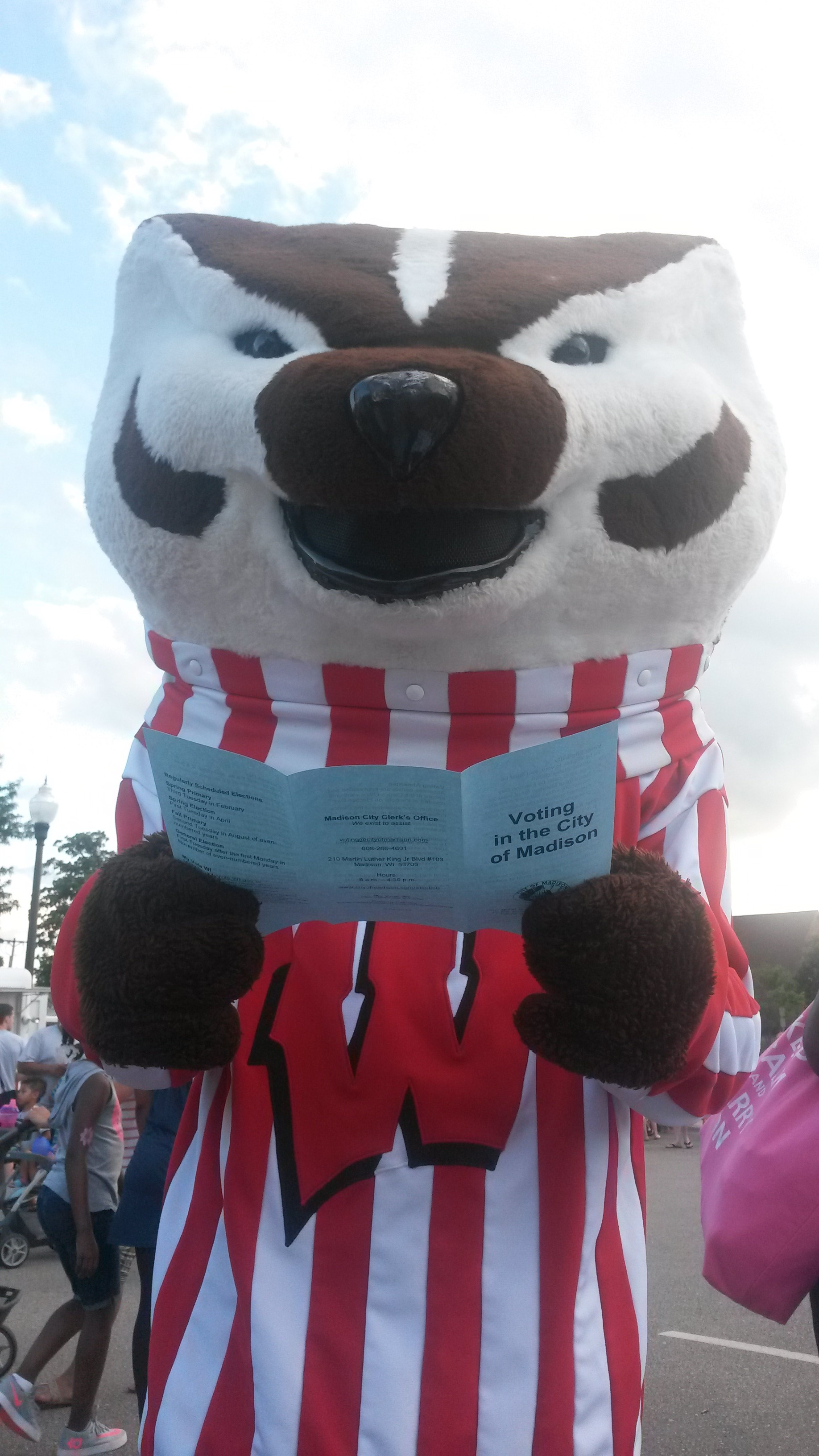 Bucky Badger mascot holding a brochure titled Voting in the City of Madison