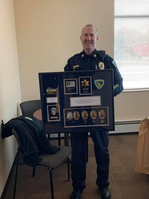 Captain Nelson holding a plaque that honors his career of service.