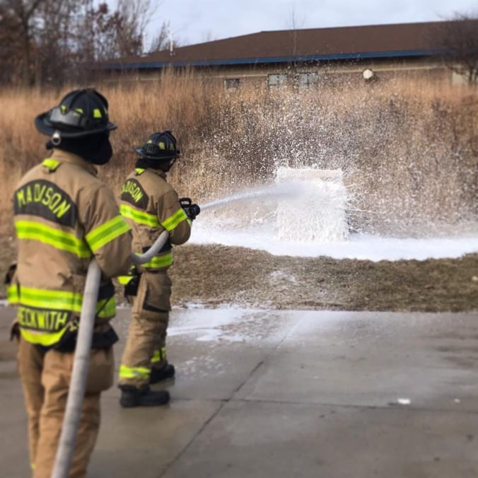 Fire fighters spraying foam onto a target