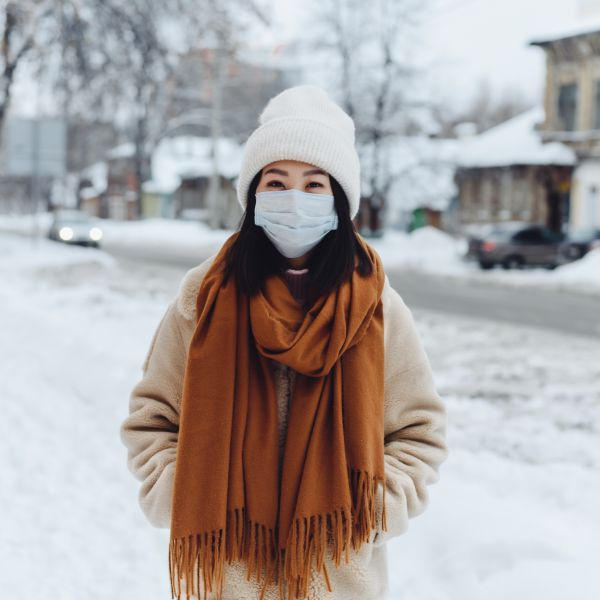 adult woman standing outside abiding public health orders by wearing a face mask