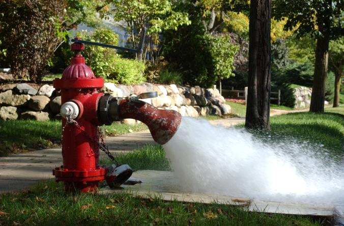 A fire hydrant with its valve opened and water flowing out