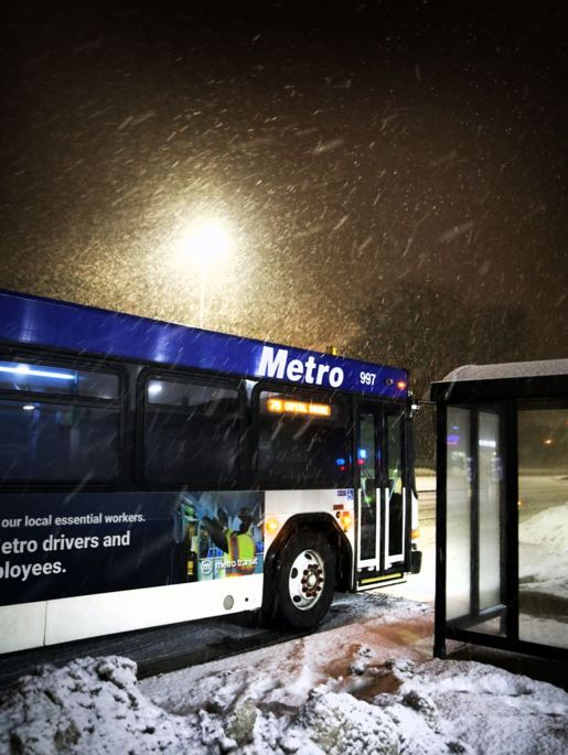 Metro bus at a busstop on a snowy night