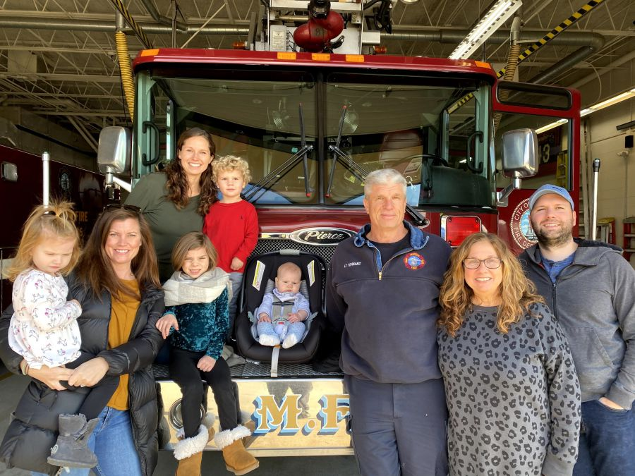 Lt. Steve Tennant with family by ladder truck