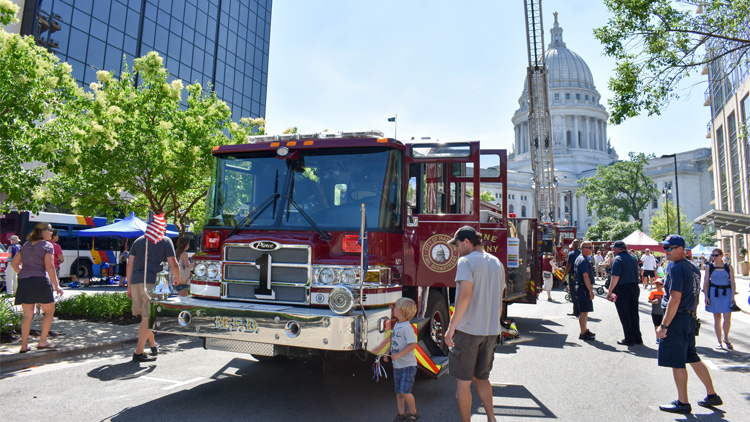 A fire truck with its doors open is parked on the street for the Safety Saturday event. The Capitol building and another fire truck with the ladder extended are in the background. Several residents and firefighters are walking nearby.