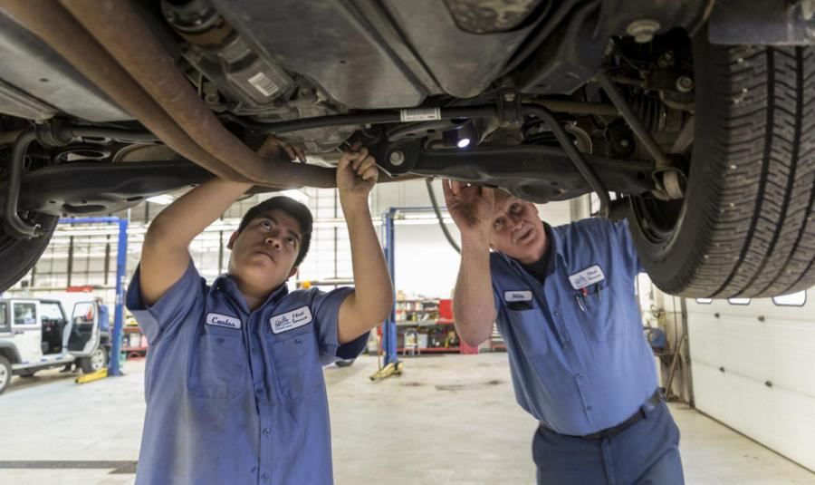 Apprentice and technician work on vehicle