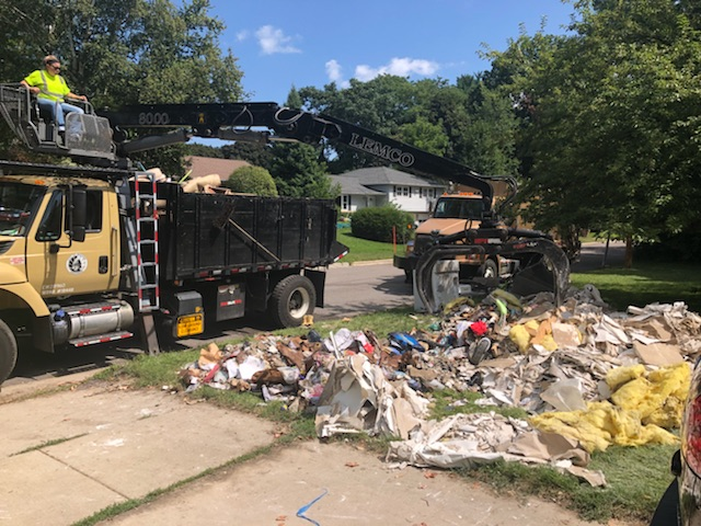 A Streets Division truck picks up large items from a front yard after the August 2019 flood.