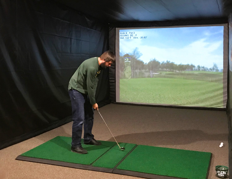 Golfer standing on green mat addressing a golfball and preparing to swing at a screen with a projected image of a fairway.
