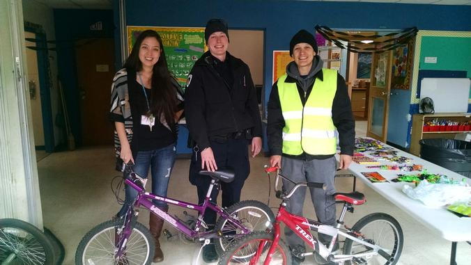 Lisa King, Ofc. Kim Alan and Beck Mugford stand with two bikes donated to the Bayview Community Center