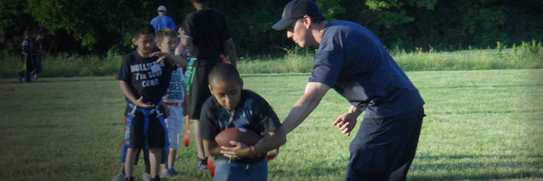 Officer playing flag football with children