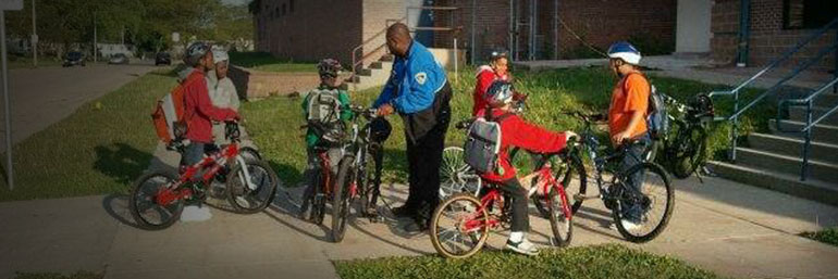 Officer helping children with bikes