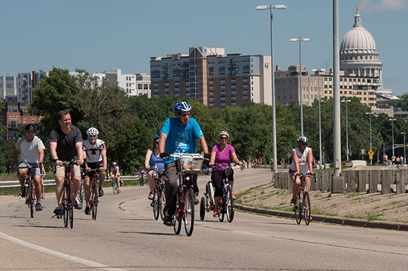 Several people bicycling on a main road. The capitol building is visible in the background.