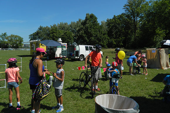 Several parents and children wearing bike helmets play yard games.