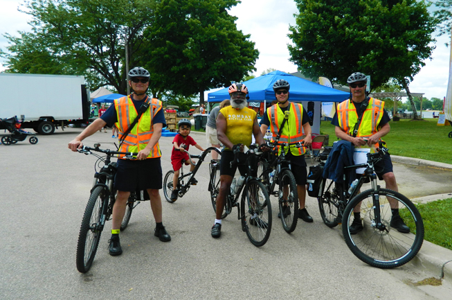 Four adults stand next to their bikes. Three of the adults wear yellow reflective vests. The fourth adult has a small child on a trail-a-bike behind his bicycle.