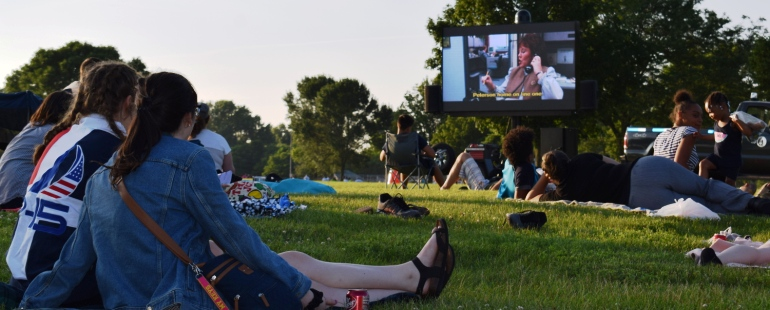 people watching an outdoor movie in a park