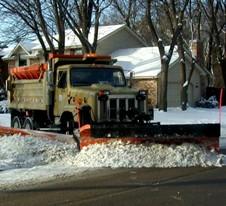 Snow plow with wing rounding a corner