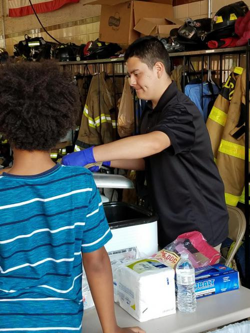 Abe Ruiz serves food at Firefighter Fun Day