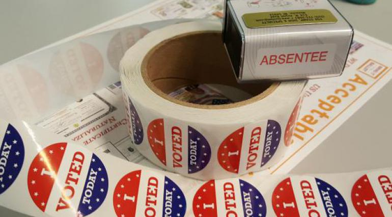 I Voted stickers, absentee envelope, and absentee stamp
