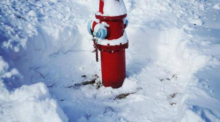 A path is cleared around a fire hydrant surrounded by snow