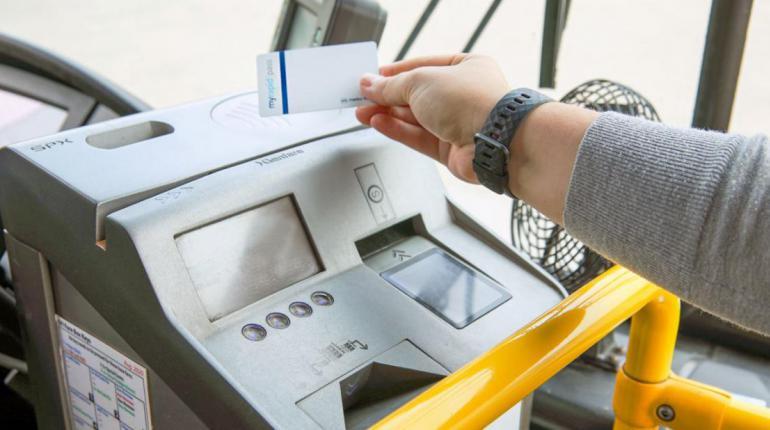hand holding a smartcard over a farebox