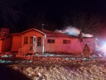 Firefighters check roof at house fire on Buckeye Road.