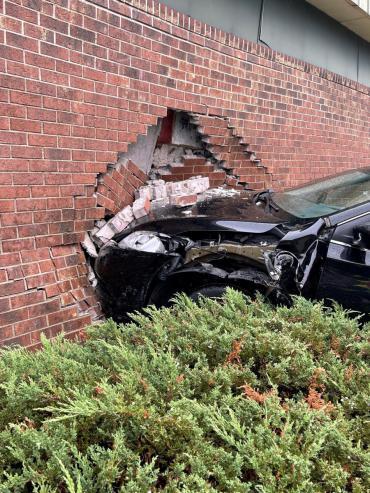 Black sedan situated against damaged brick building