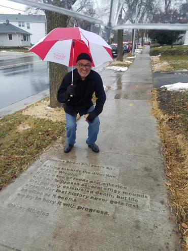 Oscar Mireles by his sidewalk poem near Wingra Park entrance on Monroe Street.