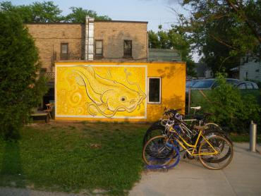 Installation shot of the mural: The word 'Yahara' means 'Catfish' (2019) by Duane Bohlman, a bright yellow painting of a catfish