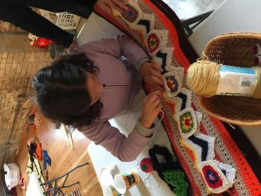 Woman works on yarn bomb section that will be applied to poll for Get Out The Vote effort Women Take the Polls
