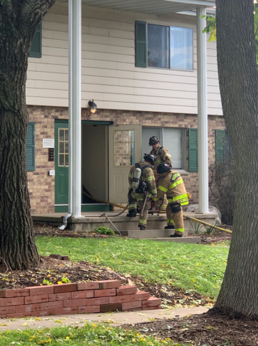 Firefighter entering apartment building on E. Karstens Drive