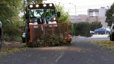A pile of leaves and yard waste being pushed by a Streets Division collection vehicle.
