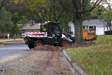 Leaf collection vehicle pulling yard waste from the terrace. Pickup begins April 6. Expect delays.