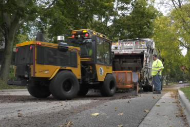 A Streets Division collecion vehicle pushes leaves into a rear-loading truck.
