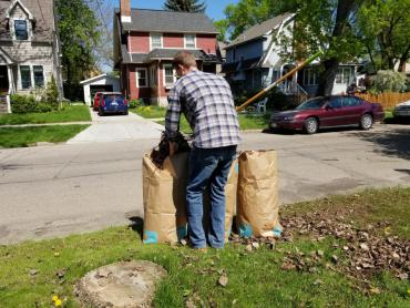 Resident placing yard waste in a compostable paper bag out for pickup