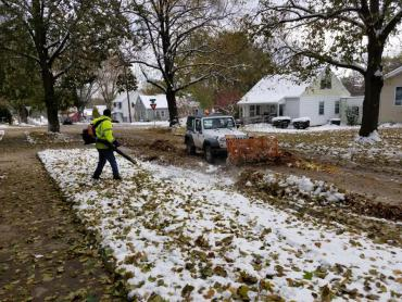 Leaf collection in the snow. Blowing leaves so they can be pushed into a truck.