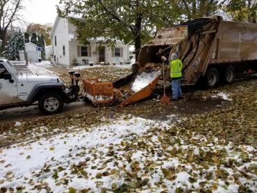 Leaf collection in the snow. Pushing leaves into a rear-loading truck.