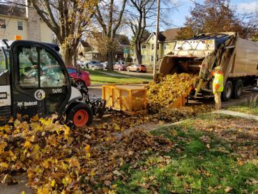 Photo from 2019 of leaf collection crews pushing leaves into a truck.