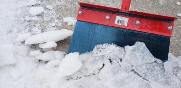 A photo of a salt pavement scraper that helps with manual removal of snow and ice.