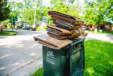 Cardboard correctly piled up on top of a recycling cart.