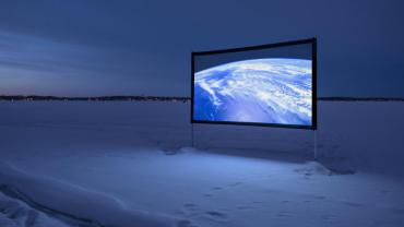 Artist Adriana Barrios films and projects on frozen lake near Spring Harbor for her Winter is Alive piece Synchronous Gaze