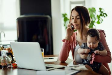 Person talking on phone while baby sits on their lap