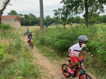 children riding bikes on park trail