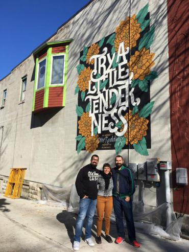 Artists Jackson Alves, Cyla Costa, with project organizer Henrique Nardi stand before Otis Redding memorial mural