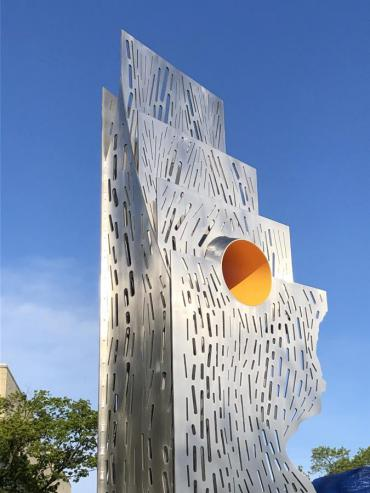 """Detail of the top portion of """"Both/And – Tolerance/Innovation"""" showing the yellow portal that intersects the vertical steel"""