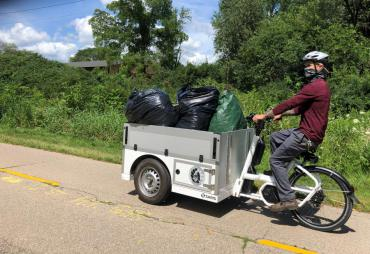 City employee using E-Bike to remove Japanese Hedge Parsley along bike path