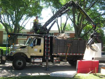 Streets Division employee using the truck-mounted crane to grab large items from the curb