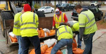 Photo of sandbag collection crew from 2018 lifting sandbags into a loader
