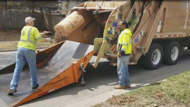 Bagged yard waste being tossed into a collection truck