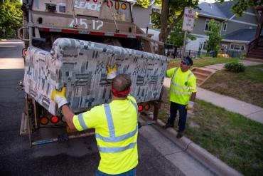 Two hearty Streets Division employees lifting a couch. Remember to follow the guidelines to make their job safer!