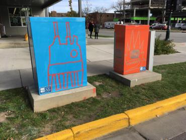 Images of two utility boxes wrapped with Derrick Buish's abstract paintings
