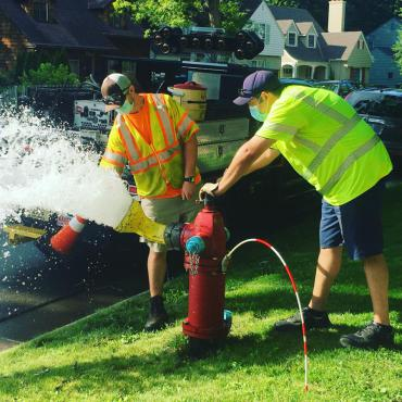 Two Madison Water Utility employees wearing masks and safety vests are working at a fire hydrant. Water sprays from the hydrant as one employee opens it and the other collects a water sample.